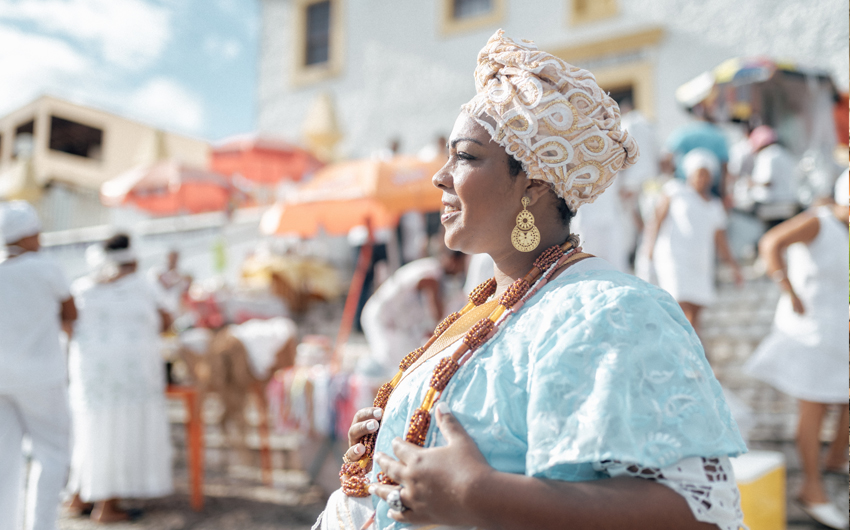 Baiana in traditional costume in front of church in Salvador
