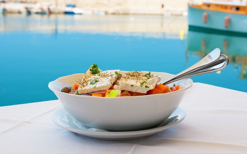 Greek salad with feta cheese on table in Crete